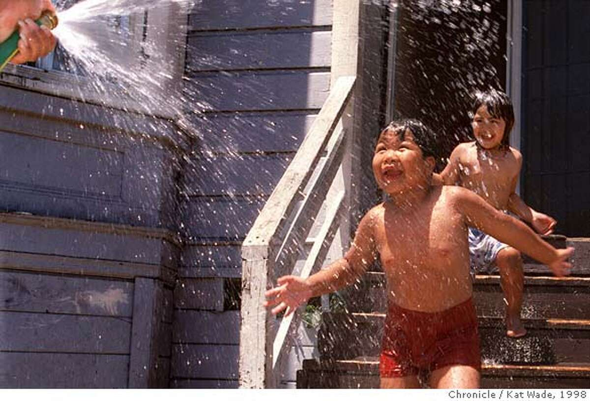 HEATWAVE1/C/16JUL98/MN/KW - Getting relief from the first day of the heat wave that has hit the Bay area, 7-year-old Bunna Phun and his listtle sister Bunnie, 6, get squirted with a hose by their big sister V (CQ), 16 in front of their Oakland home on thecorner of Foothill Blvd and 12th Avenue Thursday afternoon. SAN FRANCISCO CHRONICLE PHOTO BY KAT WADE