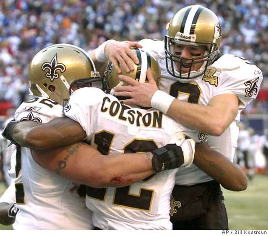 New Orleans Saints quarterback Drew Brees, right, and center Jeff Faine, left, celebrate with wide receiver Marques Colston after Colston scored a touchdown during second quarter NFL football against the New York Giants Sunday, Dec. 24, 2006 at Giants Stadium in East Rutherford, N.J. The Saints won 30-7. (AP Photo/Bill Kostroun) Photo: Bill Kostroun
