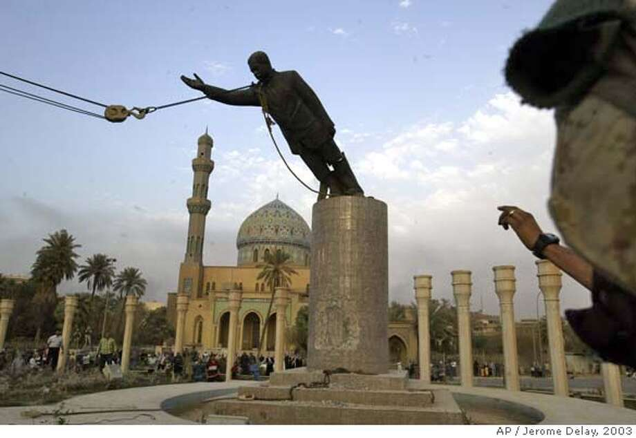 **FILE** A U.S. Marine watches a statue of Saddam Hussein being toppled in Firdaus Square, in downtown Bagdhad in this April 9, 2003 file photo. State-run Iraqi television says Saddam Hussein has been hanged Saturday Dec. 30, 2006. (AP Photo/Jerome Delay, File) Photo: JEROME DELAY