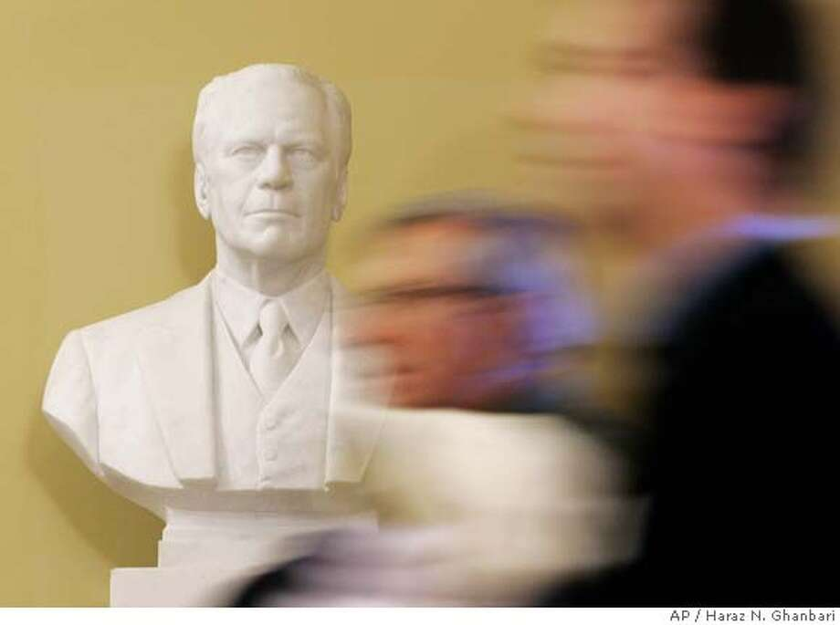 Visitors walk past a bust of President Gerald R. Ford on display near the Senate Chambers, Thursday, Dec. 28, 2006 at the U.S. Capitol in Washington. Ford will lie in state in the Capitol begining Saturday, Dec. 30, 2006. (AP Photo/Haraz N. Ghanbari) Photo: HARAZ N. GHANBARI