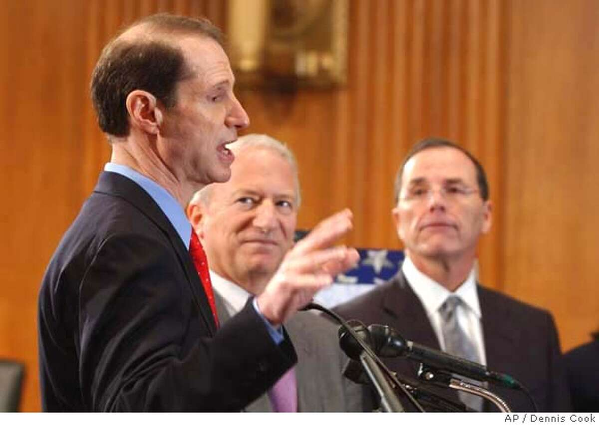 Sen. Ron Wyden, D-Ore., left, discusses his plan for affordable health care during a news conference on Capitol Hill in Washington Wednesday, Dec. 13, 2006. From left are, Wyden, Service Employees International Union (SEIU) President Andy Stern, and Safeway President Steve Burd. (AP Photo/Dennis Cook)