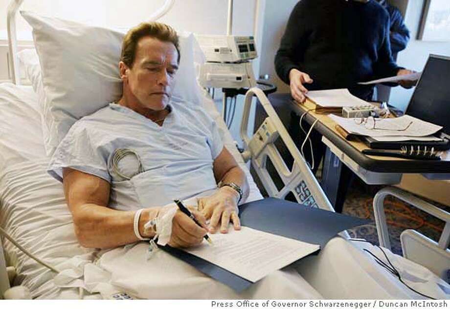 In this photo provided by the Press Office of Governor Schwarzenegger, California Gov. Arnold Schwarzenegger signs an order creating the Public Employee Post-Employment Benefits Commission in his hospital room in Santa Monica, Calif., Thursday, Dec. 28 2006. Schwarzenegger is recovering from leg surgery that followed a skiing accident in Idaho. (AP Photo/Press Office of Governor Schwarzenegger, Duncan McIntosh) PHOTO PROVIDED BY THE PRESS OFFICE OF GOVERNOR SCHWARZENEGGER Photo: Duncan McIntosh