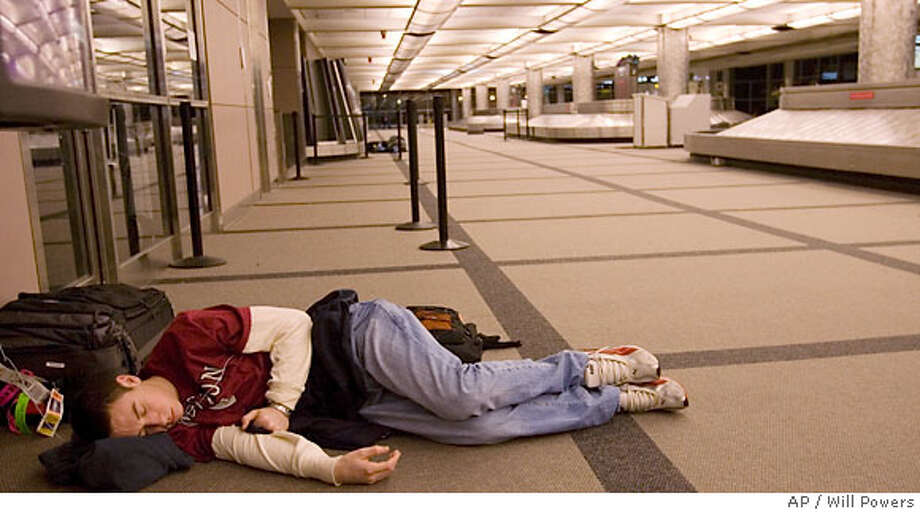 A man sleeps on the floor at Denver International Airport early Friday, Dec. 29, 2006 where he spent the night after a second snow storm hit the Denver area delaying and canceling some flights. (AP Photo/Will Powers) Photo: Will Powers