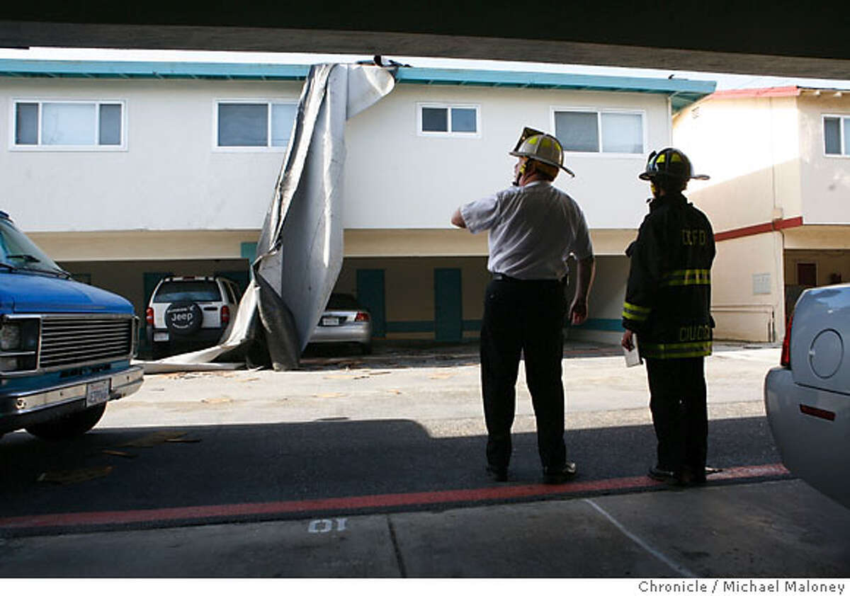 North County Fire Authority Deputy Chief Steve Brandvold (left) and PIO officer Angelina Ciucci (also of North County Fire) inspect part of the roof from another apartment complex on Esplanade Drive that had blown off the roof. Twenty units of the Ocean View apartments on Esplanade Drive in Pacifica, CA. were evacuated on Wednesday, December 27, 2006 after strong wind gusts tore part of the roof off. Photo by Michael Maloney / San Francisco Chronicle ***Angelina Ciucci , Steve Brandvold