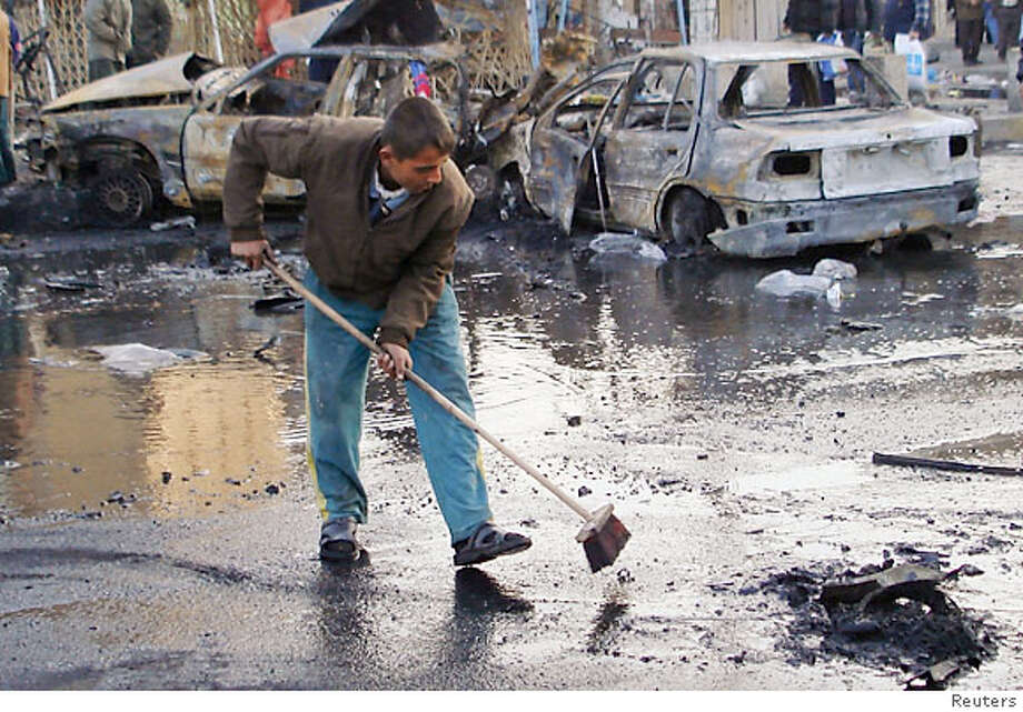 A man removes debris from a road after Tuesday's car bomb attack in Baghdad December 27, 2006. Bombs killed nearly 40 people in Baghdad, including 20 in western Adhamiya district, on Tuesday, according to the police. REUTERS/Stringer (IRAQ) Photo: STRINGER/IRAQ