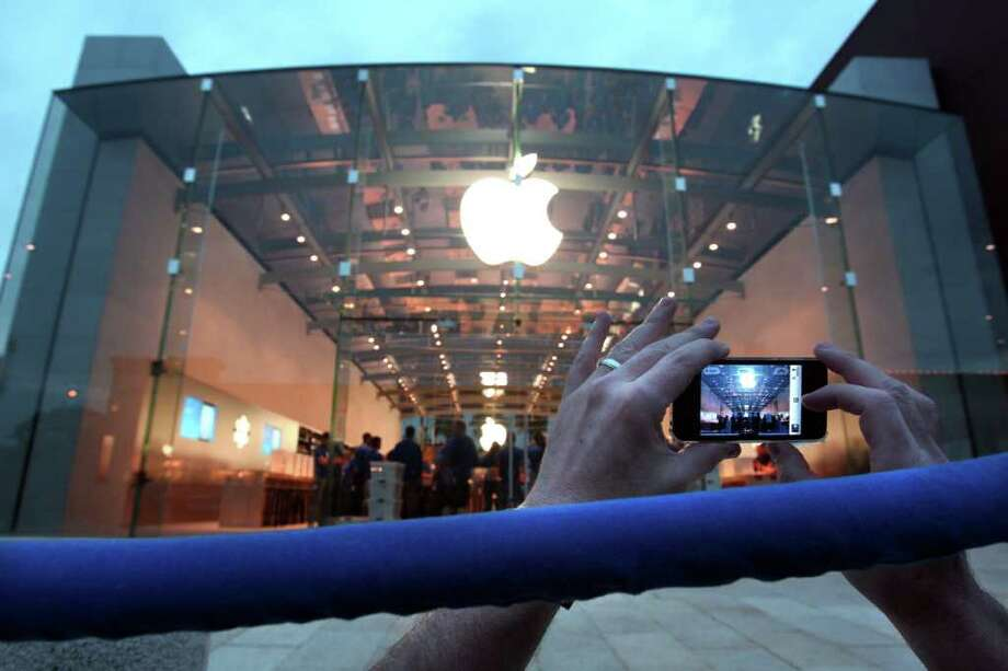 "A self-proclaimed ""Apple fanatic,"" Jeff Burke, takes a picture of the Highland Village Apple Store during its grand opening Friday, March 16, 2012, in Houston. Photo: Johnny Hanson, Houston Chronicle / © 2012 Houston Chronicle"