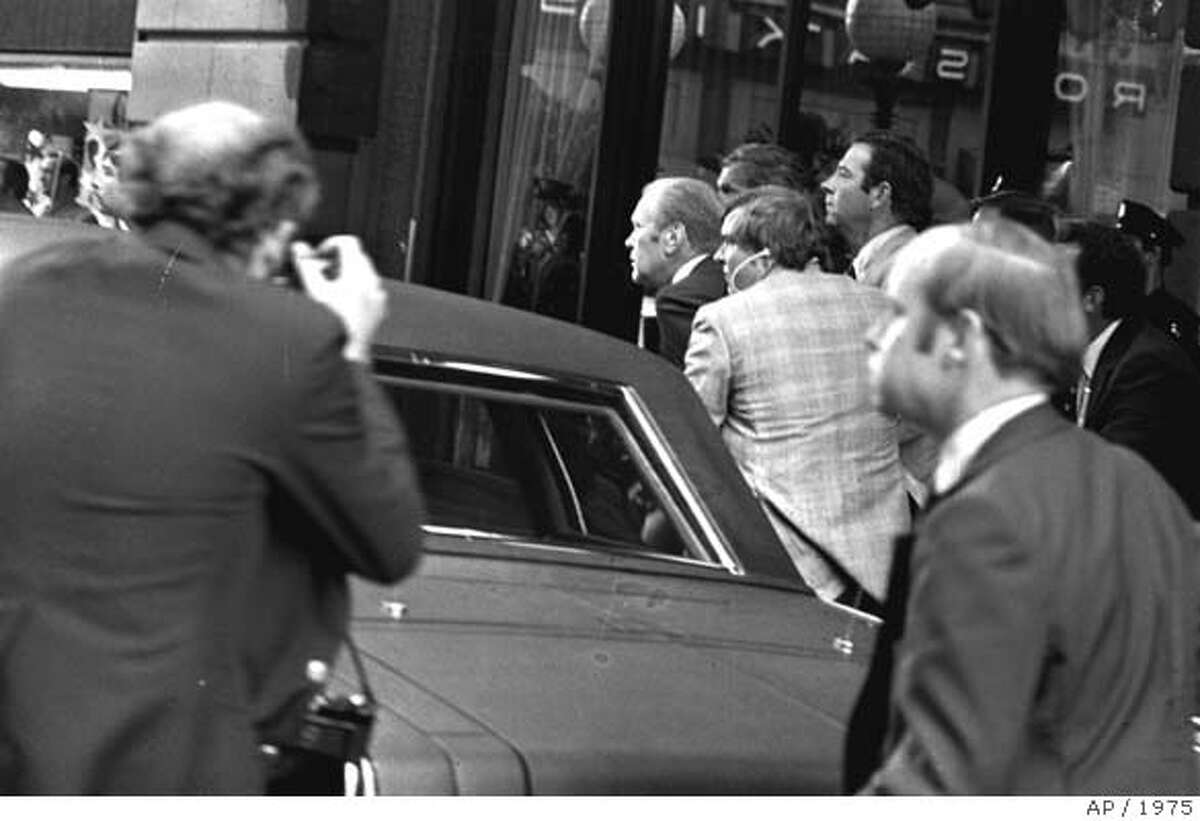 *** FILE *** President Ford ducks behind his limousine and is hustled into the vehicle after a shot was fired as he left the St. Francis Hotel in San Francisco, September 22, 1975. The President was rushed to the airport to return to Washington. Gerald R. Ford, who picked up the pieces of Richard Nixon's scandal-shattered White House as the 38th and only unelected president in America's history, has died, his wife, Betty, said Tuesday Dec. 26, 2006. He was 93. (AP Photo)