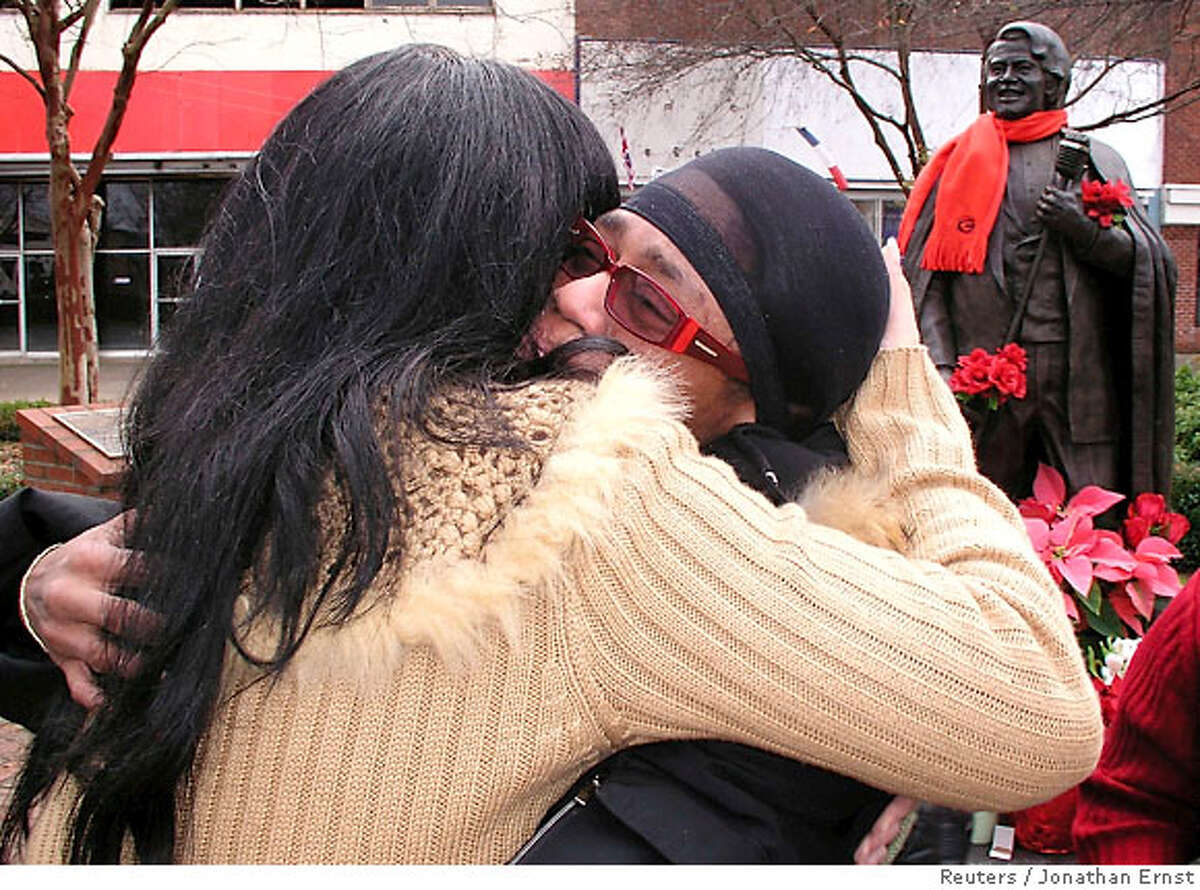 """Venisha Brown (R) hugs a friend at the base of a statue of her father, deceased singer James Brown, in his hometown of Augusta, Georgia, December 25, 2006. James Brown, known around the world as the """"Godfather of Soul"""", died early Christmas morning in Atlanta. REUTERS/Jonathan Ernst (UNITED STATES)"""