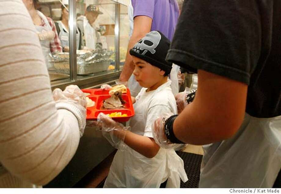 FOODHANDOUT25_0021_KW_.jpg  Gabriel Clamar, 8, from Castro Valley, was one of the youngest volunteers serving prime rib meals at Glide Memorial's annual Christmas Eve lunch. The Church estimates they served prime rib to 1,500 to 2000 on Christmas Eve December 24, 2006.  Kat Wade/The Chronicle Mandatory Credit for San Francisco Chronicle and photographer, Kat Wade, Mags out Photo: Kat Wade