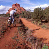 Jonathan Garza, 15, of Peoria, Ariz. rides his mountain bike on the Bell Rock trail near Sedona, Sunday, Dec. 1, 2002. His family spent the Thanksgiving holiday camping amid the red rocks. (Arizona Republic photo by Christine Keith)