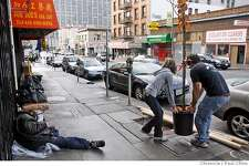 Danielle Farmer and Michele Torrano (cq) drop off a tree for planting while a man sleeps on the sidewalk (left) when volunteers helped the Friends of the Urban Forest plant 30 trees in the Tenderloin neighborhood in San Francisco, Calif. on Saturday, Dec. 9, 2006.  PAUL CHINN/The Chronicle  **Danielle Farmer, Michele Torrano (cq) MANDATORY CREDIT FOR PHOTOGRAPHER AND S.F. CHRONICLE/ - MAGS OUT