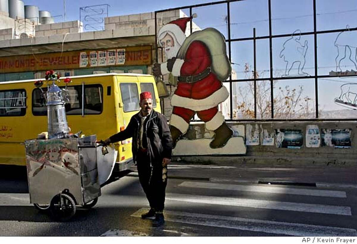A Palestinian traditional juice vendor passes a Santa Claus decoration on a street in the West Bank town of Bethlehem, Tuesday, Dec. 19, 2006. (AP Photo/Kevin Frayer)