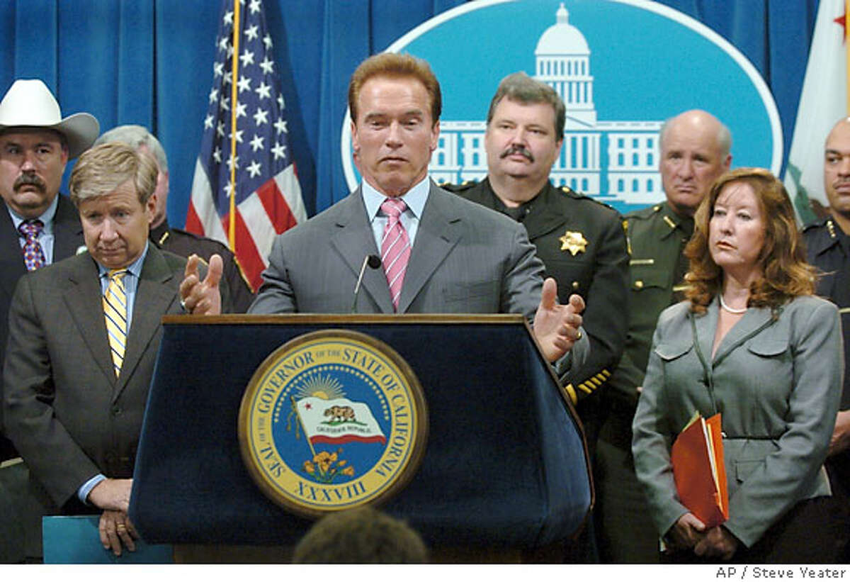 California Gov. Arnold Schwarzenegger, center, is joined by Sen. George Runner, R-Antelope Valley, left, and Sen. Gloria Romero, D-Los Angeles, right, as he talks about plans for prison reform during a news conference at the Capitol in Sacramento, Calif., Thursday, Dec. 21, 2006. (AP Photo/Steve Yeater)