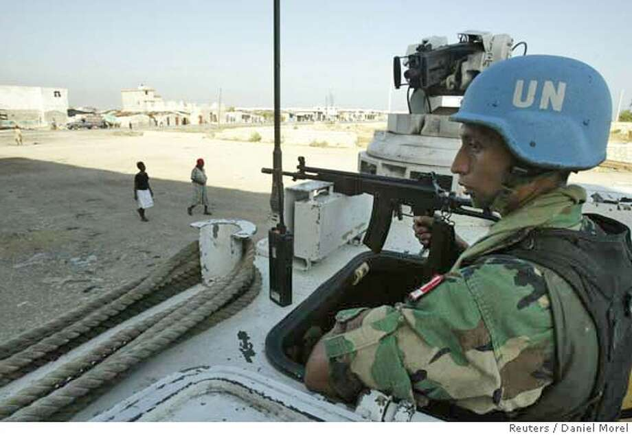A Peruvian UN peacekeeper keeps guard at a UN checkpoint inside the slum of Cite Soleil, Haiti, on April 15, 2005, a day after a Philippine peacekeeper was shot in the head and killed by gang members in the same zone. He was the fourth peacekeeper to be killed since the mission started last summer. The United Nations Security Council continued their four-day visit to Haiti today, and in meetings stressed the importance of supporting a UN-Haitian police disarmament effort slated to start soon. REUTERS/Daniel Morel Ran on: 04-16-2005  A Peruvian U.N. peacekeeper guards a checkpoint inside the Haitian slum of Cit� Soleil, an area prone to violence. ALSO Ran on: 05-16-2005  U.N. troops in Haiti Ran on: 05-16-2005  U.N. troops in Haiti  Ran on: 12-22-2006  A Peruvian U.N. peacekeeper guards a checkpoint inside Cite Soleil, Haiti. Many Haitians say the mission has done little to stop crime. Photo: DANIEL MOREL