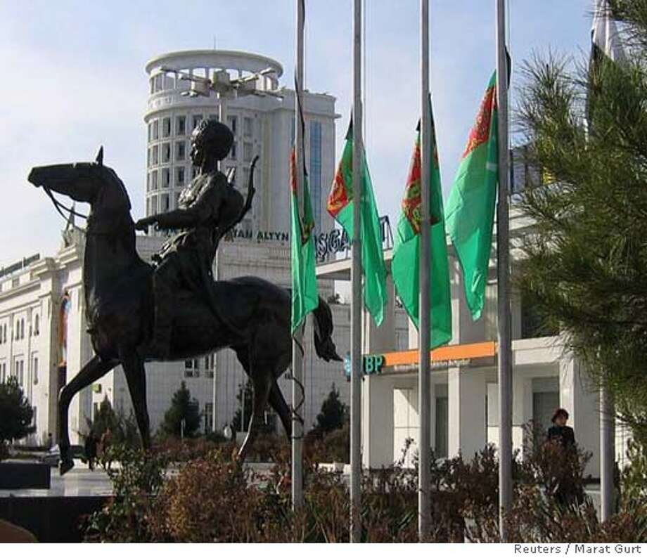 A pedestrian walks past national flags flying at half-mast in Ashgabat December 21, 2006. Turkmenistan's President-for-life Saparmurat Niyazov died on Thursday after 21 years of iron rule in which he crushed all dissent and made his Central Asian state one of the world's most isolated countries. State television and government sources said Niyazov, 66, whose country has the world's fifth-biggest reserves of natural gas, died overnight of cardiac arrest. REUTERS/Marat Gurt (TURKMENISTAN) 0 Photo: STAFF