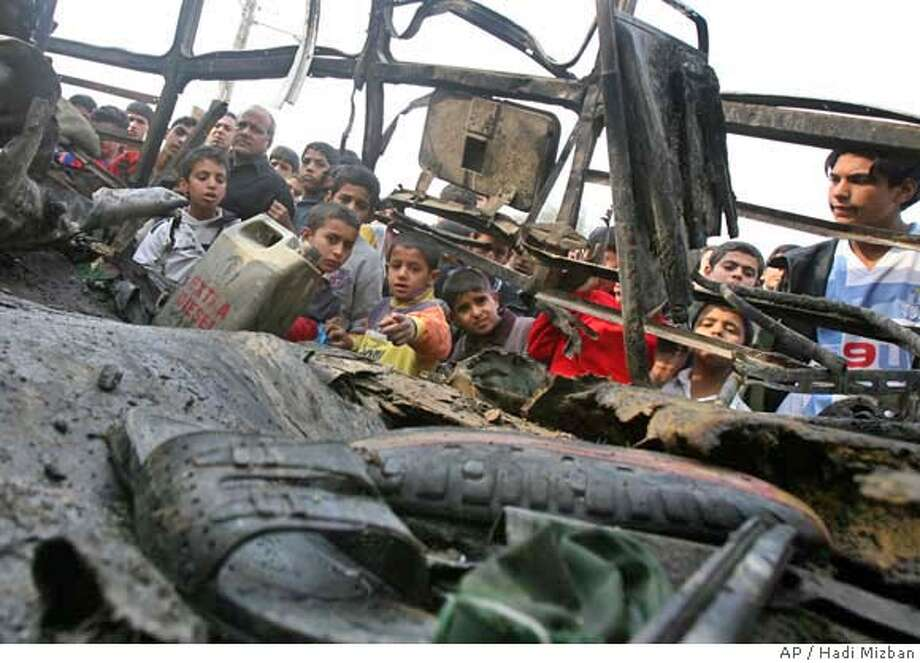Iraqis inspect the wreckage of a bus following an explosion in Baghdad, Iraq, Wednesday, Dec. 6, 2006. A suicide bomber with explosives hidden beneath his clothing set them off aboard a bus in the Sadr City district of Baghdad, killing two people and wounding 15, police said. (AP Photo/Hadi Mizban) Photo: HADI MIZBAN