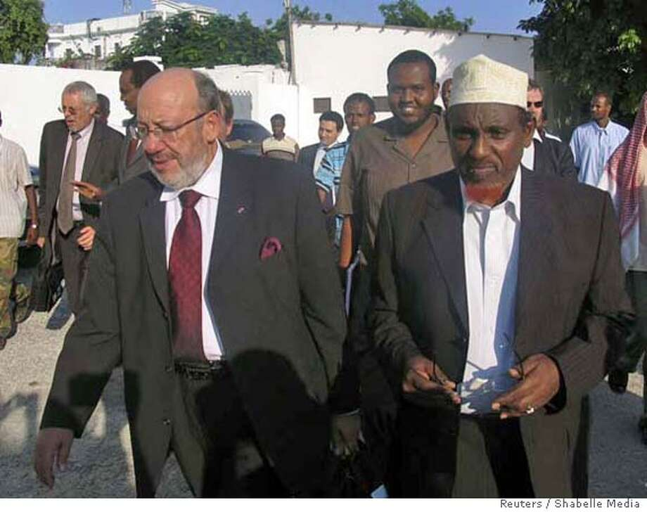 Leader of Somalia Islamic Courts Sheikh Hassan Dahir Aweys (R) and European Union aid chief Louis Michel (front, L) walk in Somalia's capital Mogadishu December 20, 2006. Somali Islamists and troops defending the government's only stronghold battled with rockets and heavy weapons on Wednesday at two frontline areas, but Sheikh Aweys denied it was the start of war. REUTERS/Shabelle Media (SOMALIA) 0 Photo: STR