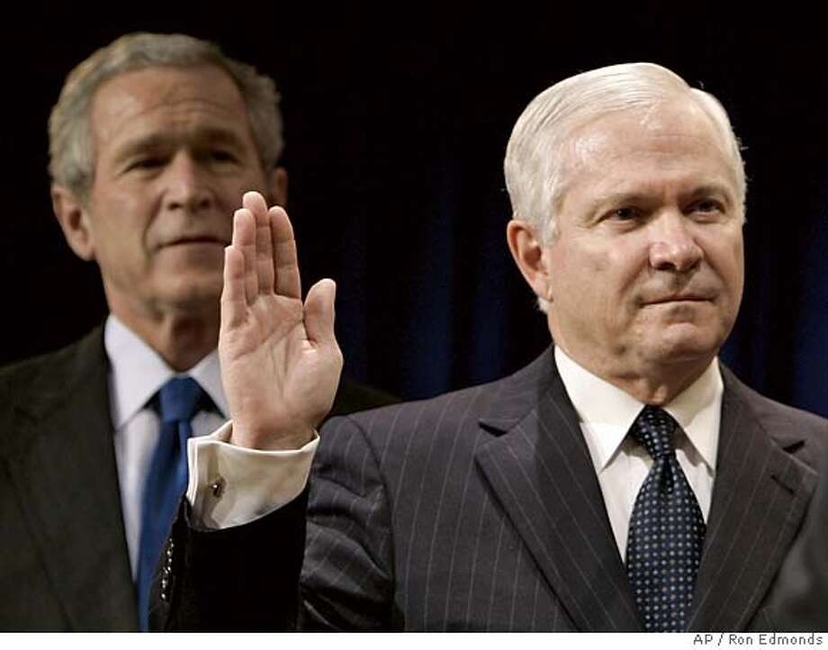 President Bush, left, watches as Defense Secretary Robert Gates is sworn in by Vice President Dick Cheney, not shown, during a ceremony at the Pentagon, Monday, Dec. 18, 2006. (AP Photo/Ron Edmonds) Photo: RON EDMONDS
