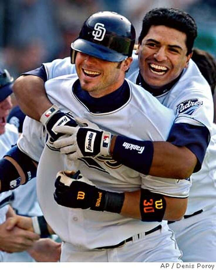 San Diego Padres' Ryan Klesko, left, is hugged by the Padres' Miguel Ojeda after Klesko hit a three-run home run off of Arizona Diamondbacks pitcher Matt Mantei in the ninth inning Sunday, April 18, 2004, in San Diego. The home run gave the Padres a 6-5 win. (AP Photo/Denis Poroy) Two games ended on ninth-inning homers. At left, the Phillies' Doug Glanville exults after beating Montreal. At right, Ryan Klesko lifts the Padres, including Miguel Ojeda, on his broad shoulders. Photo: DENIS POROY