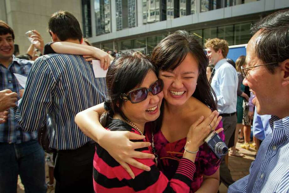 Fourth-year medical student Jingyi Li, center, is hugging her mother, Jin Long, as her father, Ping Li, right, looks on during Match Day ceremonies at the Baylor College of Medicine. Li was matched in anesthesiology at Weill Cornell Medical Center in New York. The ceremony is a physicians' rite of passage. After four years of medical school, the medical students rip open envelopes to learn where they will perform residencies, the next step in their medical careers. Photo: Smiley N. Pool, Houston Chronicle / © 2012  Houston Chronicle
