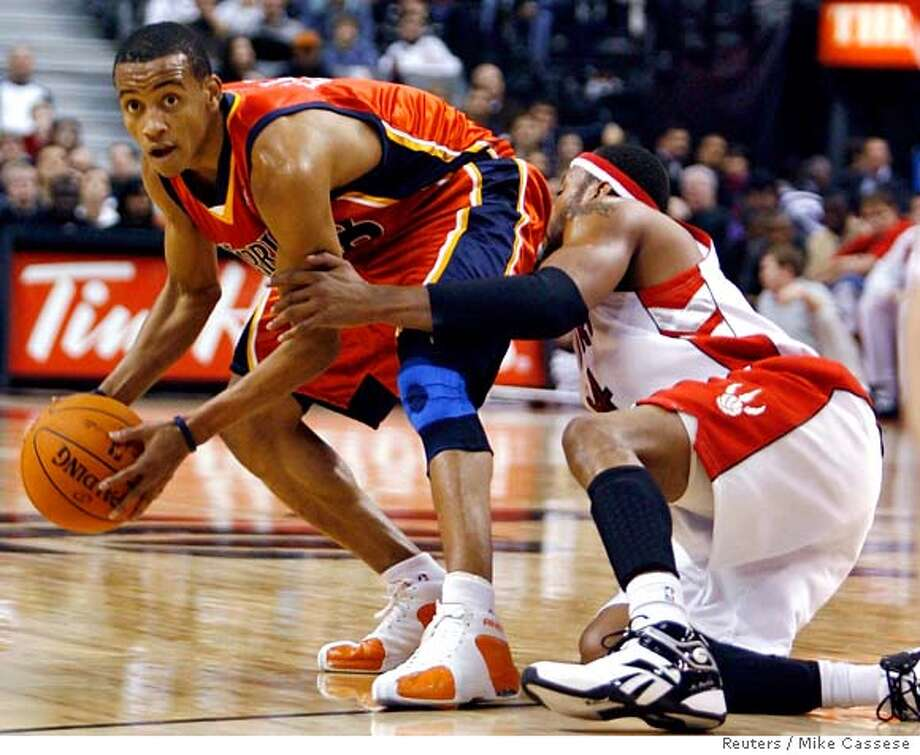 Golden State Warriors guard Monta Ellis (L) recovers a loose ball against Toronto Raptors' Morris Peterson during the first half of their NBA game in Toronto December 17, 2006. REUTERS/Mike Cassese (CANADA) 0 Photo: MIKE CASSESE