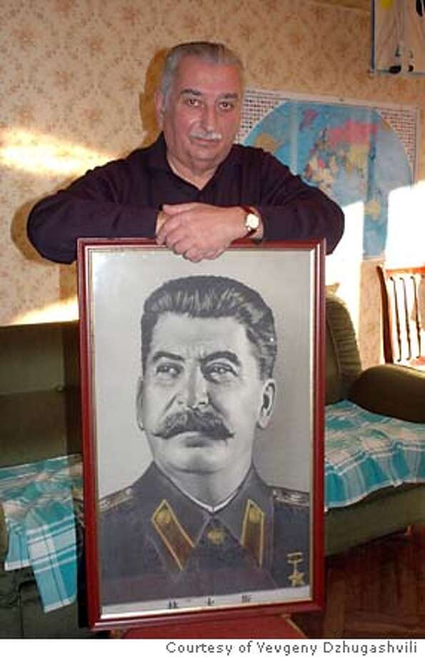 Portrait of Joseph Stalin with grandson holding framed portrait Photo: Yevgeny Dzhugashvili
