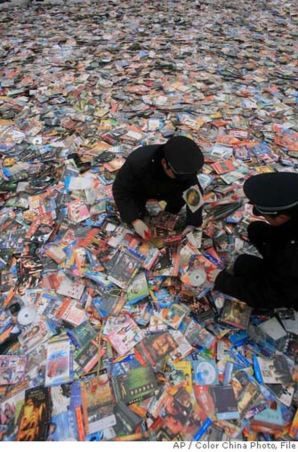 ** FILE ** Officials prepare to destroy pirated CDs and DVDs in Beijing in this Dec. 8, 2006 file photo. Ahead of this week's visit to Beijing by U.S. Treasury Secretary Henry Paulson, an annual report by Schwab to Congress gave ammunition to U.S. critics of Beijing by saying China is failing to live up to its World Trade Organization market-opening commitments. The report said Beijing should do more to fight product piracy, end policies that favor Chinese companies and lower barriers to foreign competitors in its service industries. (AP Photo/Color China Photo/File) ** CHINA OUT ** CHINA OUT DEC. 8, 2006 FILE PHOTO Photo: Ap