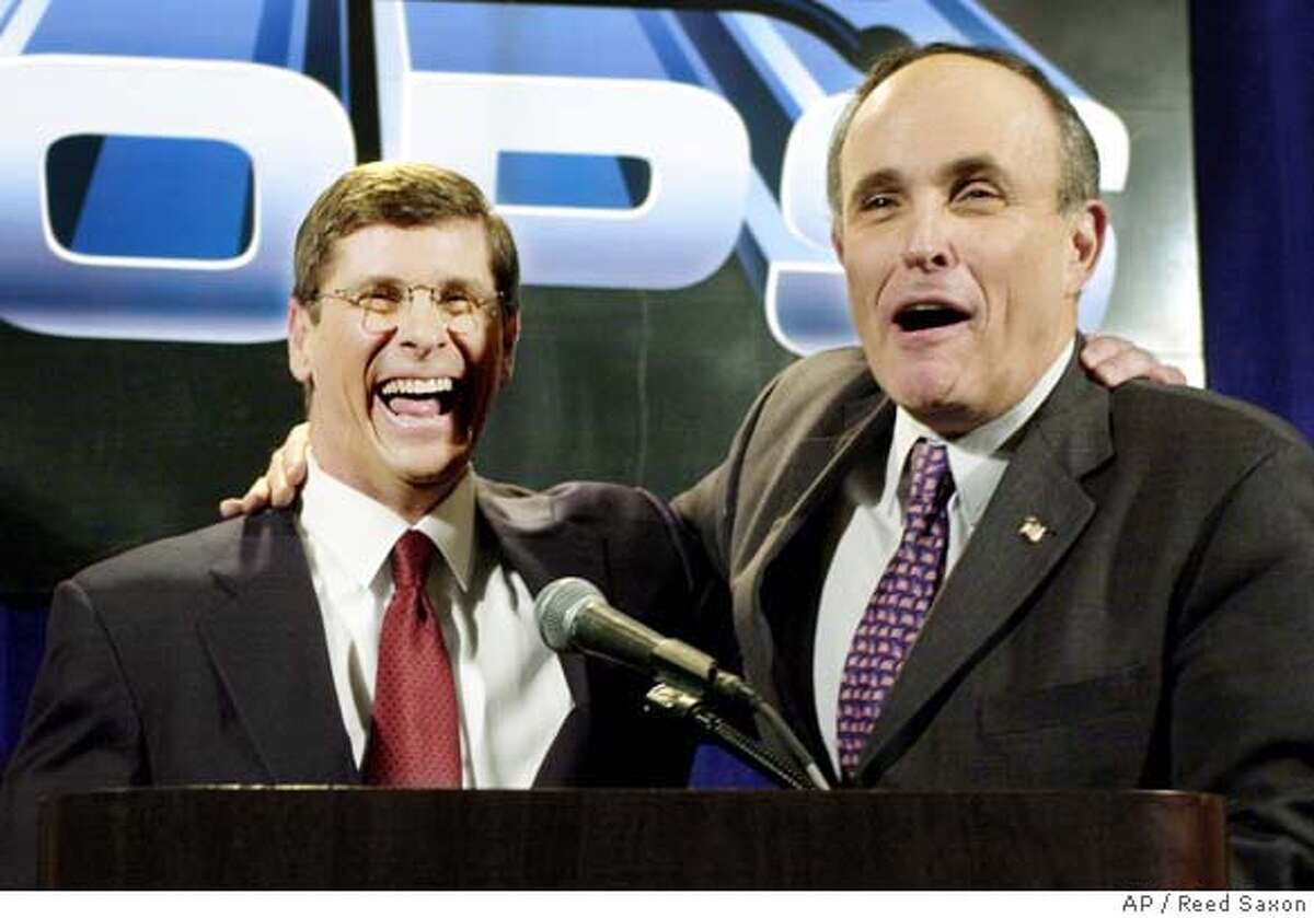 """Former New York City Mayor Rudolph Giuliani, right, shares a happy moment with California Republican gubernatorial candidate Bill Simon, a former Giuliani assistant when both were federal prosectors, at a news conference before a Simon fundraising luncheon Thursday, Jan. 17, 2002, at the Century Plaza Hotel in Los Angeles. """" California could not get a better man than Bill Simon,"""" Giuliani said. Simon, now a Los Angeles businessman, is seeking the GOP nomination to face incumbent Democrat Gray Davis. Simon trails former Los Angeles Mayor Richard Riordan and Secretary of State Bill Jones in the most recent statewide poll. (AP Photo/Reed Saxon) DIGITAL IMAGE"""