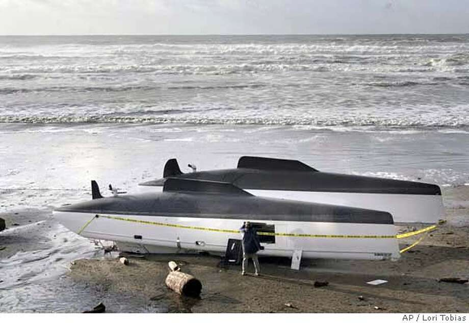 A catamaran was found washed up on the beach near Road's End in Lincoln City, Ore., Friday morning, Dec. 15, 2006. The Coast Guard is searching the central coast for the three members of the crew whose boat was spotted wrecked only about 50 feet from shore at Lincoln City. A hired crew had been sailing it from South Africa to Seattle. (AP Photo/The Oregonian, Lori Tobias) NO MAGS, , Photo: LORI TOBIAS