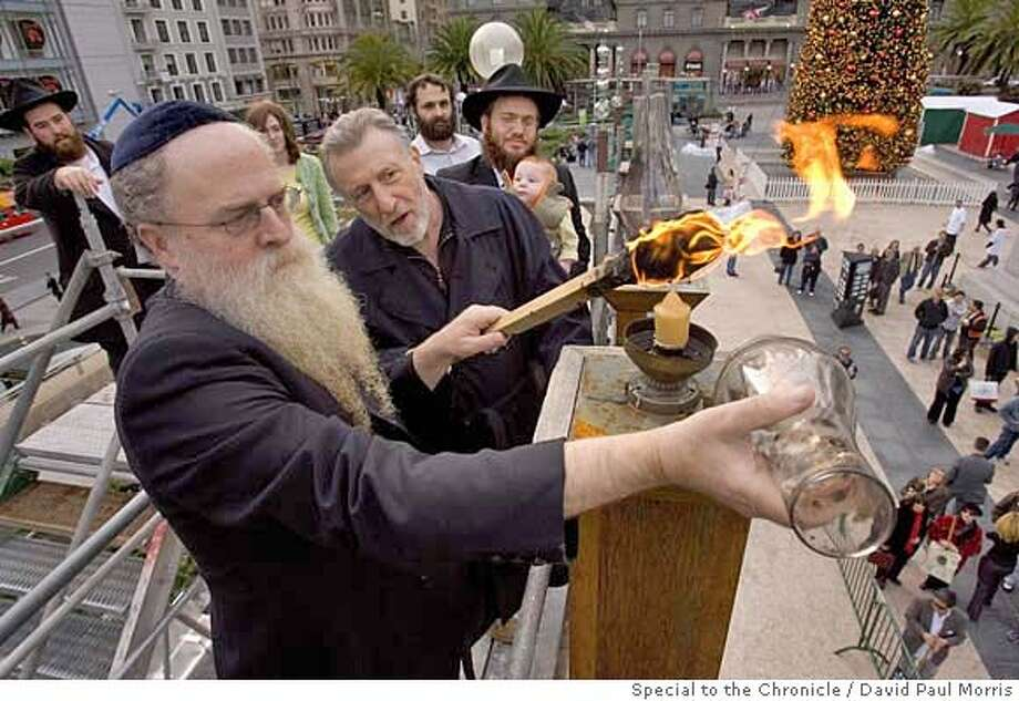 HERCULES, CA - DECEMBER 15: (L-R front row) Rabbi Yosef Langer with Chabad of San Francisco lights the first candle on the Menorah as George Zimmer, Rabbi Peretz Mochkin, 6 month old Mendel Mochkin, (back row) Jr Rabbi Moshe Lander and Miryum Mochkin look on at Union Square on the first day of Chanukah on December 15, 2006 in San Francisco, California. Photo by David Paul Morris/The Chronicle Photo: David Paul Morris