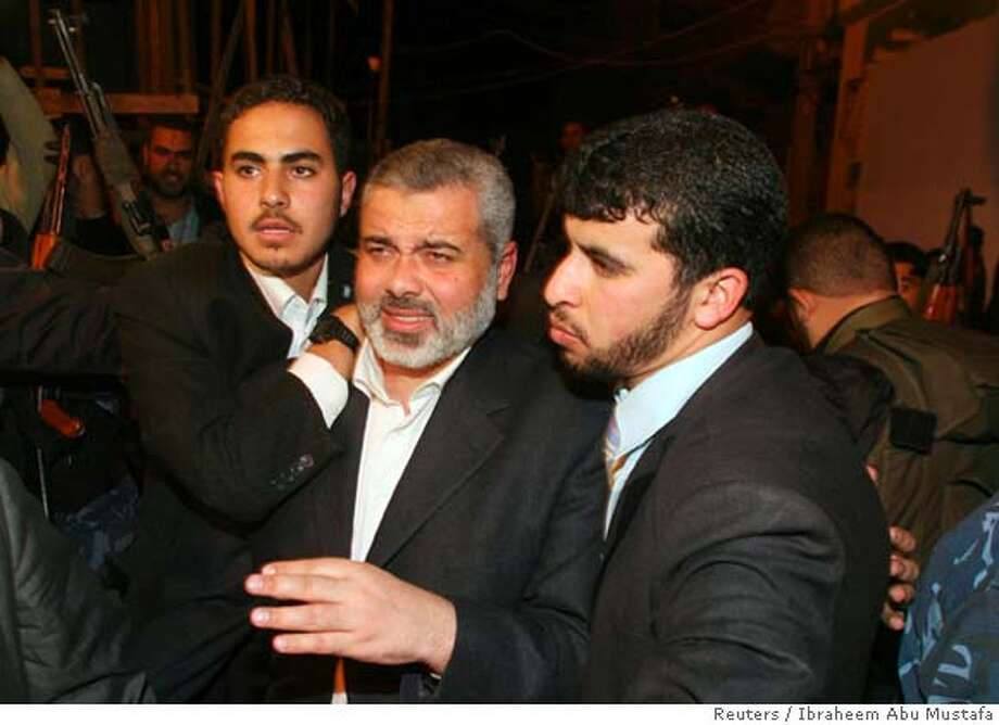 Palestinian Prime Minister Ismail Haniyeh (C) returns to the Gaza Strip December 14, 2006. Israel blocked Haniyeh from carrying $35 million into Gaza on Thursday, allowing the Hamas leader to return from fund-raising in Muslim countries only after he left the money behind. REUTERS/Ibraheem Abu Mustafa (GAZA STRIP)  Ran on: 12-15-2006  Ismail Haniyeh (center), Palestinian prime minster, returns to the Gaza Strip after a border standoff.  Ran on: 12-15-2006 Photo: IBRAHEEM ABU MUSTAFA
