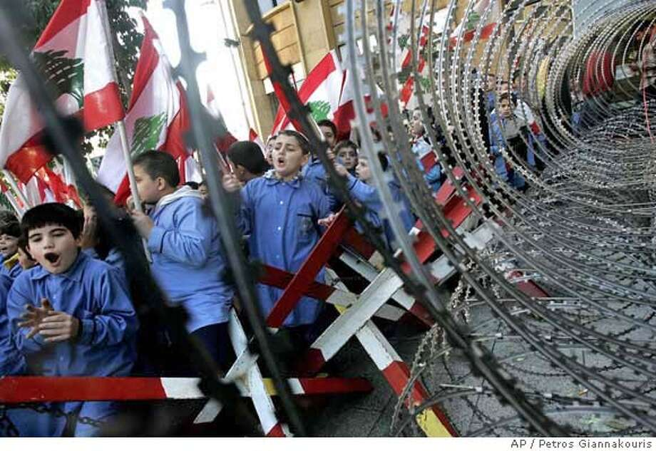 Lebanese school children wave Lebanese flags as they stand beside a barbed wire security perimeter erected outside Government House, as they take part in the fourteenth day of an open-ended protest to try and force the resignation of Lebanese Prime Minister Fuad Saniora, in central Beirut, Lebanon, Thursday Dec. 14, 2006. The Shiite Muslim group Hezbollah and its allies are threatening to bring down the Saniora government unless it is reformed to give them a greater share of power. Saniora, who is backed by anti-Syrian politicians who dominate parliament, has so far refused to back down. (AP Photo/Petros Giannakouris) Photo: PETROS GIANNAKOURIS
