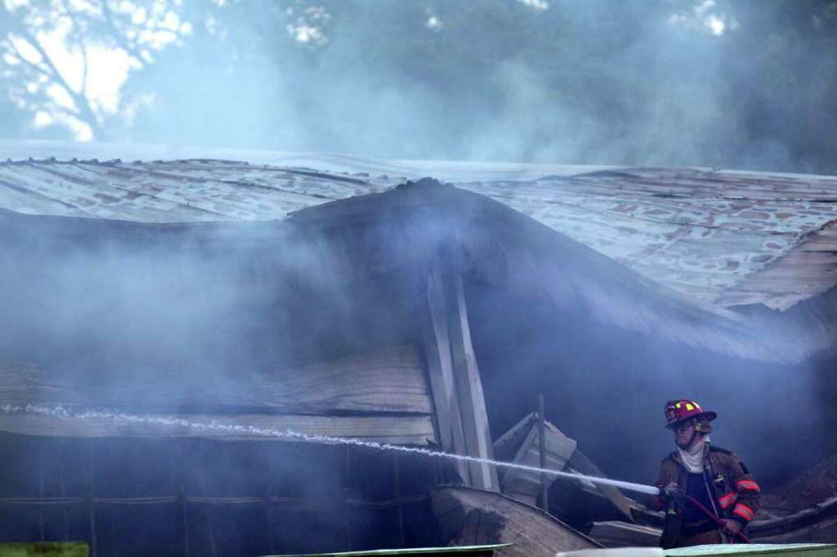 A firefighter works on hosing down what was left of the White Elephant Flea Market. Portions of the building's roof and walls had collapsed during the blaze.