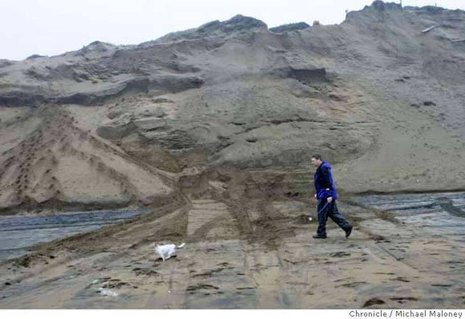 """John Eggert of San Francisco walks his dog 'Luna"""" along the beach past the steep cliffs where a man was buried alive earlier in the day. Eggert who often walks his dog along the beach has often seen a man in his 50's sleeping in the area. Eggert can be reached at (650) 483-0561. The cliff in the background was bulldozed in an effort to look for the man any others who may have been buried.  A man was found dead at the south end of Ocean Beach this morning, December 14, 2006 after he apparently was smothered by sand while he slept on the shore, officials said. A person walking a dog on the beach near Sloat Boulevard about 8:15 a.m. spotted a hand sticking out of the sand and notified authorities  Photo by Michael Maloney / San Francisco Chronicle  ***John Eggert Photo: Michael Maloney"""