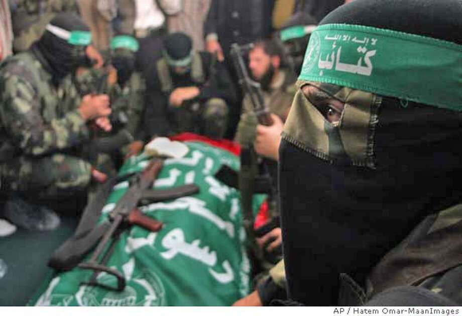 Palestinan masked militants from Hamas gather around the body Bassam al-Fara, a local Hamas leader, during his funeral in Khan Younis, in the southern Gaza Strip, Wednesday, Dec. 13, 2006. Palestinian gunmen forced the Hamas commander to his knees and fatally shot him early Wednesday outside the courthouse where he worked as an Islamic judge, escalating factional tensions in the Gaza Strip and prompting the Palestinian prime minister to cut short a trip abroad. (AP Photo/Hatem Omar-MaanImages) Photo: HATEM OMAR