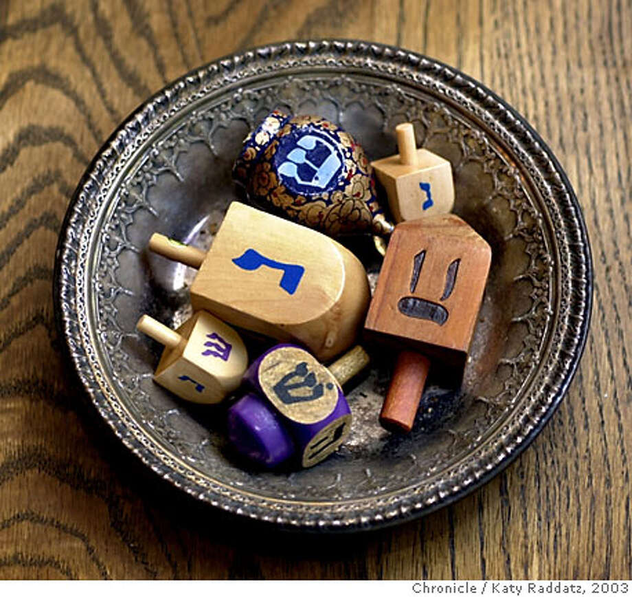 Story about celebration of Hanukkah in the home. SHOWN: At the Marker family home in Oakland we find a cute little bowl of dreidels ready to play with. Dreidels are like toy tops, with a Hebrew letter on each side. One gambles on what letter will land up. Pennies are encouraged, as is Hanukkah gelt (play money). KATY RADDATZ / The Chronicle Photo: KATY RADDATZ