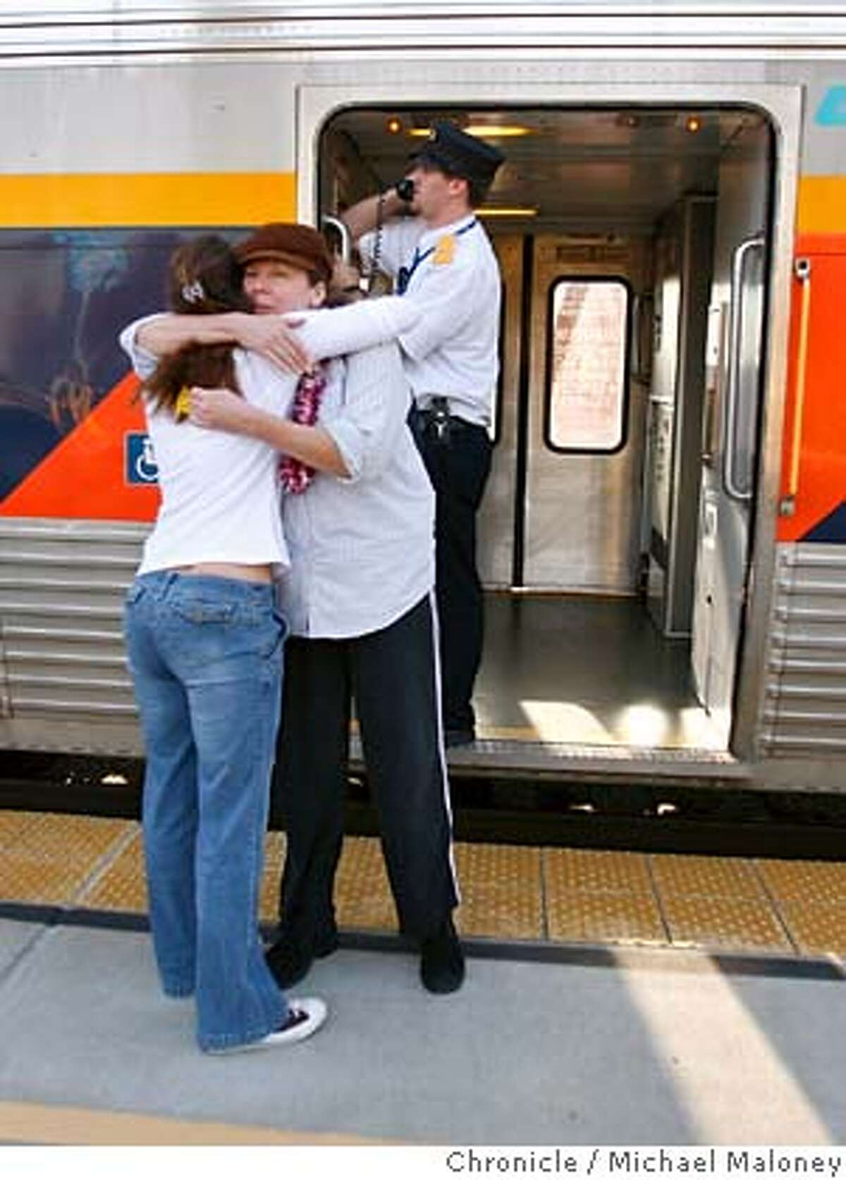 Debbie Mills of Huntington Beach, CA (facing camera) hugs goodbye to her daughter Amethyst Thomas of Danville prior to boarding a westbound Capitol Corridor train in Hayward. In background is Capitol Corridor's Matt Zundel. Mills was in Danville visiting Thomas' family, prior to heading back home. The Capitol Corridor, a train service run by parts of nearly a dozen agencies, shouldn't work. Too many bureaucrats have their hands in it and it relies on tracks heavily traveled by freight trains. But the increasingly popular commuter train service turns 15 this month and its popularity is soaring. Photo by Michael Maloney / San Francisco Chronicle MANDATORY CREDIT FOR PHOTOG AND SF CHRONICLE/ -MAGS OUT
