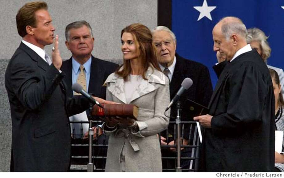 """INAUGURAL_184_fl.jpg; Arnold Schwarzenegger Schwarzenegger was sworn in today on the steps with his wife Marie Shriver holding the Bible (Administered by California Chief Justice Ronald George) of the state Capitol in Sacramento as thousands of well-wishers stood by. """"I am humbled, I am moved, and I am honored beyond words to be your governor,"""" he said as an opening to his speech. """"I have taken the oath to serve you,"""" he said to all Californians. """"I will not forget my oath, and I will not forget you."""" He then thanked former Governor Gray Davis for the spirit of mutual cooperation and respect during the transition. After that, he laid out his vision. In the background is (L-R) Stan Atkinson, (MC) and his father-in-law Sargent Shriver. The Chronicle MANDATORY CREDIT FOR PHOTOG AND SF CHRONICLE/ -MAGS OUT Photo: FREDERIC LARSON"""