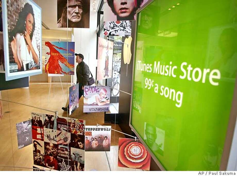 �** FILE ** Apple Computer customer walks into an Apple store in Palo Alto, Calif., Tuesday, May 6, 2003, passing a display of music albums for Applie's new iTunes Music Store. Apple Computer Inc. faces a serious challenge in France, where lawmakers have moved to sever the umbilical cord between its iPod player and iTunes online music store _ threatening its lucrative hold on both markets, Friday, March 17, 2006. (AP Photo/Paul Sakuma)Ran on: 03-18-2006 Apple's online music sales face a challenge in France, where lawmakers want the service to work with any player, not just iPods. Ran on: 07-14-2006 ITunes ads are all over the Apple Store in Palo Alto. An iPod that helped break iTunes' encryption technology sold recently. TUESDAY, MAY 6, 2003 FILE PHOTO