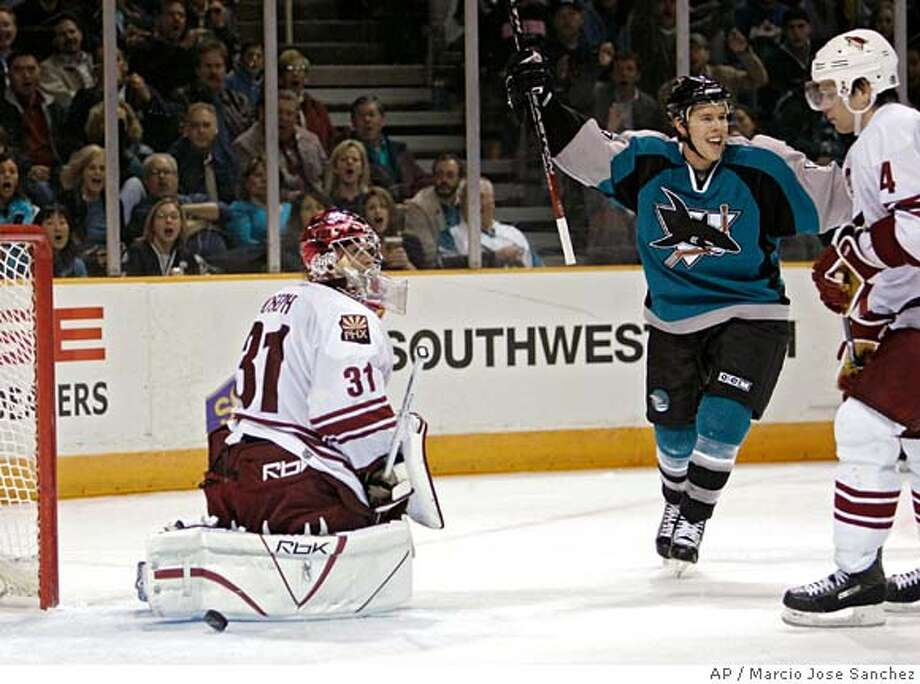 San Jose Sharks center Joe Pavelski, middle, celebrates after scoring a goal past Phoenix Coyotes goalie Curtis Joseph, left, as defenseman Zbynek Michalek (4), of the Czech Republic, looks on in the second period of an NHL hockey game in San Jose, Calif., Monday, Dec. 11, 2006. (AP Photo/Marcio Jose Sanchez) Photo: MARCIO JOSE SANCHEZ