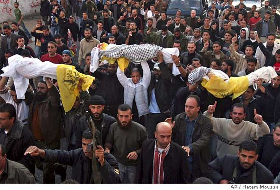 Palestinian carry the bodies of senior intelligence officer Baha Balousheh's three sons who were killed in a drive-by shooting attack, during their funeral in Gaza City, Monday, Dec. 11, 2006. Palestinian gunmen killed three young children of a senior Palestinian intelligence officer Monday, pumping dozens of bullets into their car as it passed through a street crowded with schoolchildren, an apparent botched assassination attempt that could ignite widespread factional fighting. (AP Photo/Hatem Moussa) Photo: HATEM MOUSSA