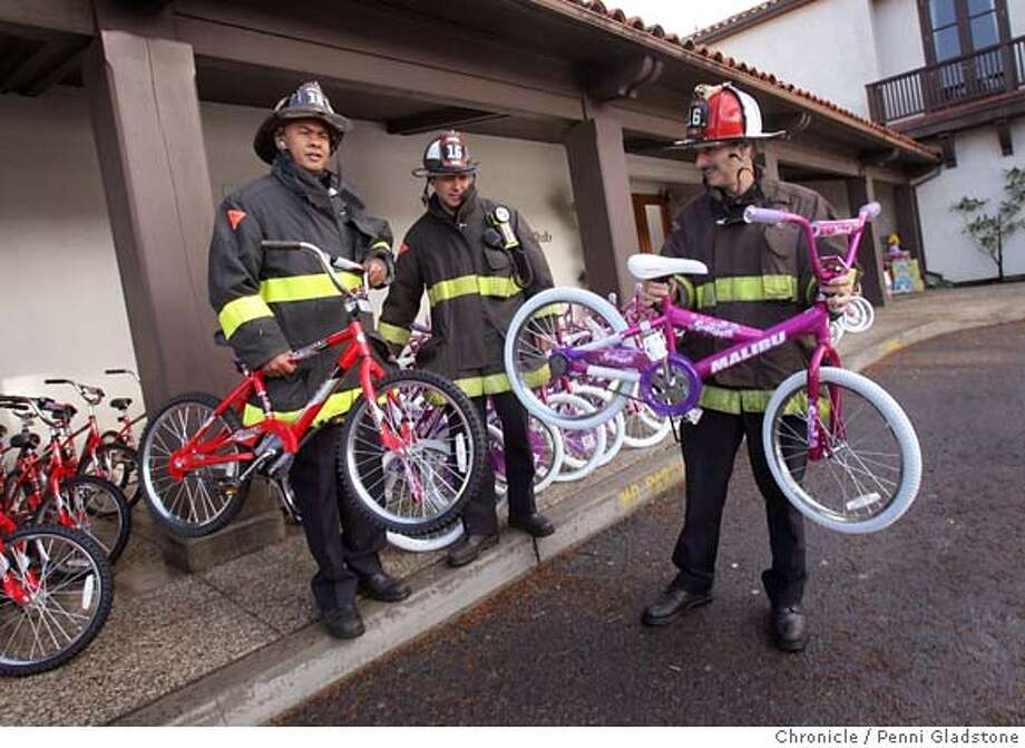 BIKES  Firefighters Doug Manguiat, & Mark O'Hara from Engine 16 and Wayne Martin of Truck 16 looking at and hefting some bikes to be given away to needy children. This took place at the St. Francis Yacht Club on Sunday outside the club headquarters on the Marina Green. This kicks off the start of the annual firefighters toy drive for disadvantaged kids. St. Francis Yacht Club members were asked to donate money to purchase these bikes, all 150 of them. It was the first year for the bikes, seventh year for toy drive. In addition, they gave over $3,000 to fire department to purchase more gifts. Event on 12/10/06 in San Francisco.  Penni Gladstone / The Chronicle MANDATORY CREDIT FOR PHOTOG AND SF CHRONICLE/ -MAGS OUT Photo: Penni Gladstone