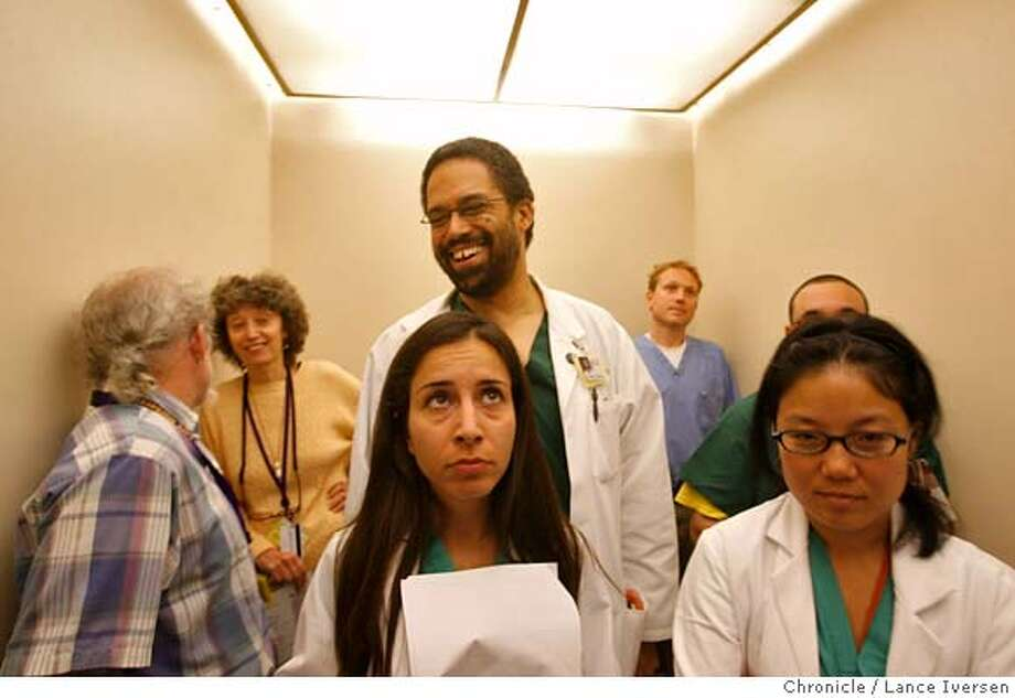 ER: San Francisco's General Hospital Chief of Staff Dr Andre Campbell (tall man center) shares a smile and light conversation in an elevator as he and his Trauma Surgery team members Doctors Rita Muktar and Lori Yueno ,head down to ER. Within minutes a 15 year old gunshot victim was admitted, sending the team into action and eventfully back up to the 3rd floor operating rooms. The unidentified victim was saved but required several operations. 6/27/06 in SAN FRANCISCO. Photo: By Lance Iversen