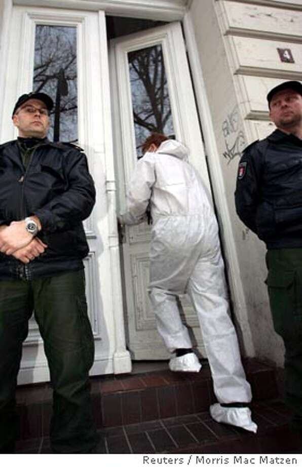 Police stand guard as a member of the federal office for radiation protection, wearing a protective suit, enters a apartment in Hamburg December 9, 2006. German police have found traces of radiation in two buildings linked to a Russian businessman who met the murdered ex-spy Alexander Litvinenko on the day he fell ill, a spokeswoman said on Saturday. Radiation traces were found overnight in an apartment in the northern German city of Hamburg belonging to the ex-wife of Russian businessman Dmitry Kovtun, who met Litvinenko in a London bar and who is also now in hospital. REUTERS/Morris Mac Matzen (GERMANY)  Ran on: 12-10-2006  Police stand guard as a radiation inspector wearing a protective suit enters an apartment in Hamburg, Germany.  Ran on: 12-10-2006  Police stand guard as a radiation inspector wearing a protective suit enters an apartment in Hamburg, Germany. Photo: STR