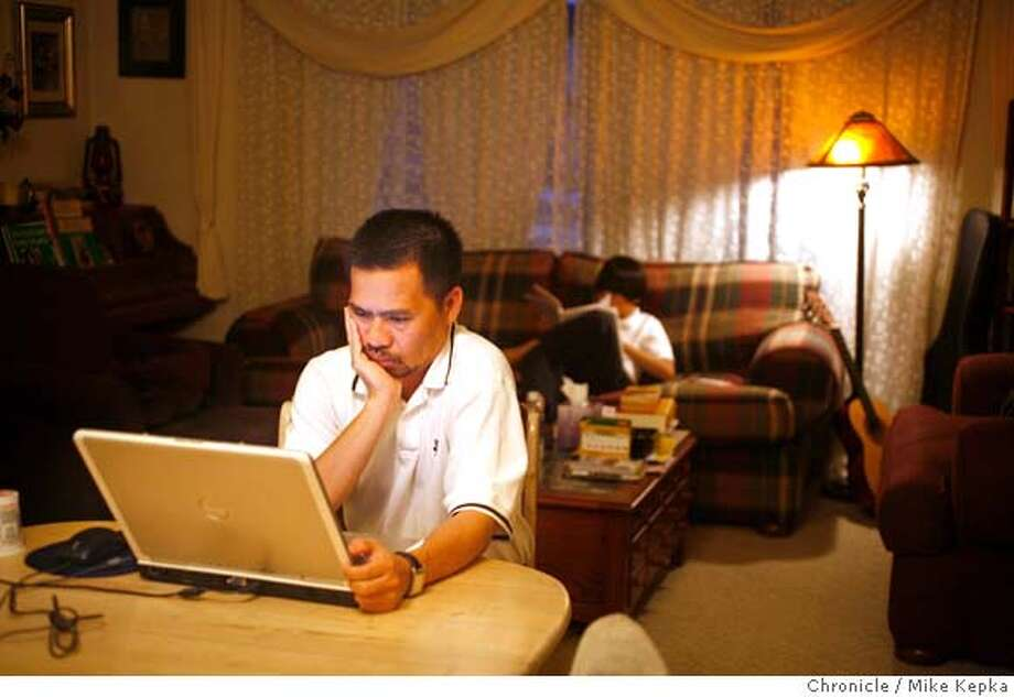 �vietnam00101_mk.JPG Cong Do checks his email as his youngest son, Nien Dobui, 10, works on homework on the living room couch. Cong Thanh Do, a Vietnamese American from San Jose, was jailed in Ho Chin Minh City for more than a month after his his home country found out he was leading a democracy initiative on-line. His family was able to get him released after being locked up for more than a month. Photo taken on 10/26/06. Cong Thanh Do Nien Dobui(cq) MANDATORY CREDIT FOR PHOTOG AND SF CHRONICLE/ -MAGS OUT Photo: Mike Kepka