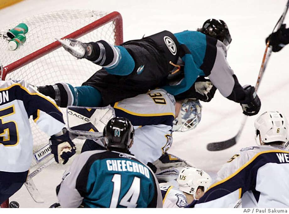 San Jose Sharks center Curtis Brown (37) jumps over Nashhville Predators goalie Chris Mason (30) as he scores in the first period of an NHL hockey game Saturday, Dec. 9, 2006, in San Jose, Calif. (AP Photo/Paul Sakuma) Photo: PAUL SAKUMA