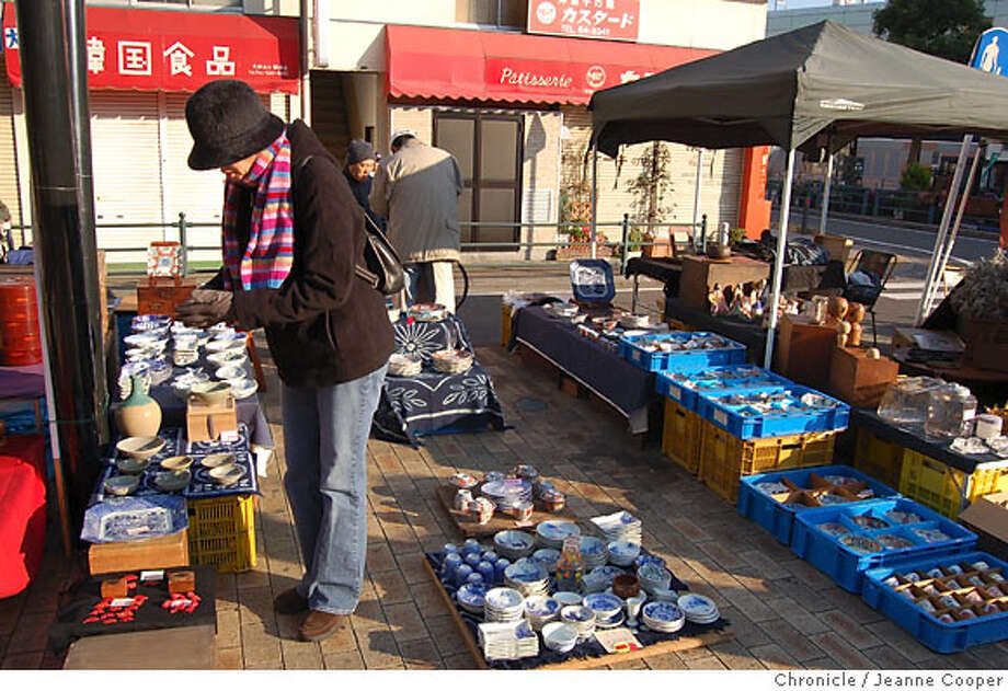 """TRAVEL JAPAN SHOP -- A shopper from the nearby Atsugi Naval Air Facility examines porcelain and ceramic items at the antiques fair in Yamato, Japan, one of many regularly held flea markets known loosely as """"shrine sales."""" Yamato on 11/17/06. Photo: Jeanne Cooper"""