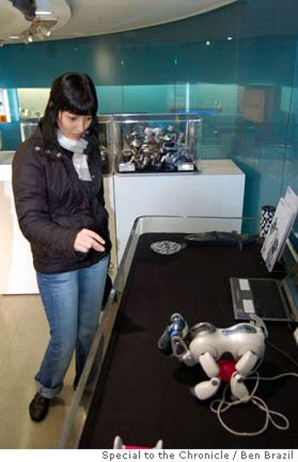 12-10-2006 pub date  Yolanda Montilla of Barcelona, Spain, plays with a robotic dog in the Sony showroom in Tokyo�s Ginza district. Japanese companies have showrooms throughout Tokyo - great places to check places to check out the latest products for free.  !!ONE TIME USE ONLY WITH SPECIAL TO CHRON TOKYO STORY!!  Photo credit: Ben Brazil  Ran on: 12-10-2006  Chuo Avenue in Tokyo's Ginza district is bustling, but you don't need bags of cash to explore the energetic capital city, despite its reputation as one of the world's priciest places. Photo: Ben Brazil