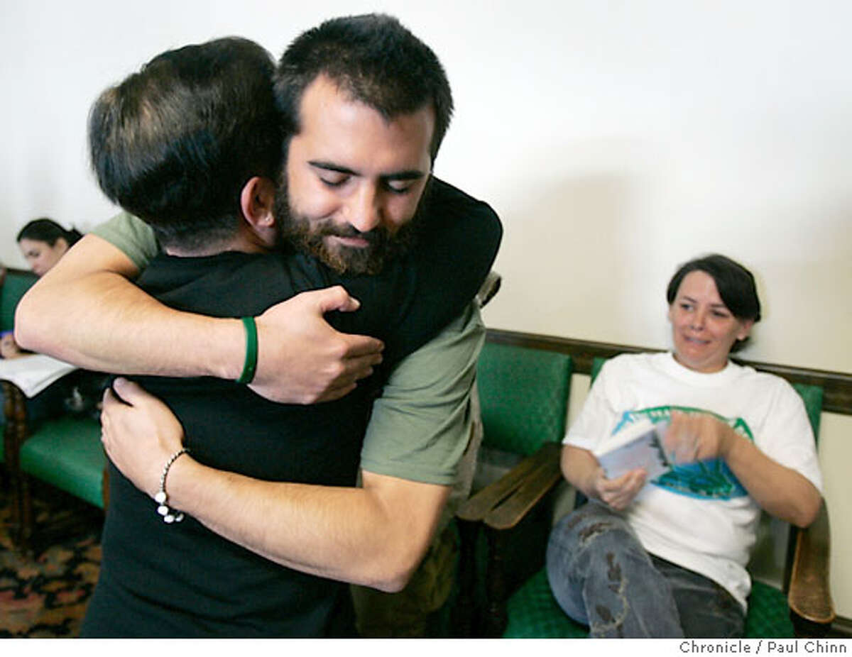 Iraq war resister Darrell Anderson hugs Rosa Sakanishi, as his mother Anita Dennis (right) cries, at a forum organized by the anti-war group Courage to Resist in San Francisco, Calif. on Saturday, Dec. 9, 2006. Anderson, deployed to Iraq as an Army soldier in 2004, fled to Canada after he concluded the war was wrong and was eventually discharged from the military. Sakanishi's stepson Ehren Watada faces a court martial for refusing his deployment to Iraq with his Army unit. **Darrell Anderson, Rosa Sakanishi, Anita Dennis, Ehren Watada