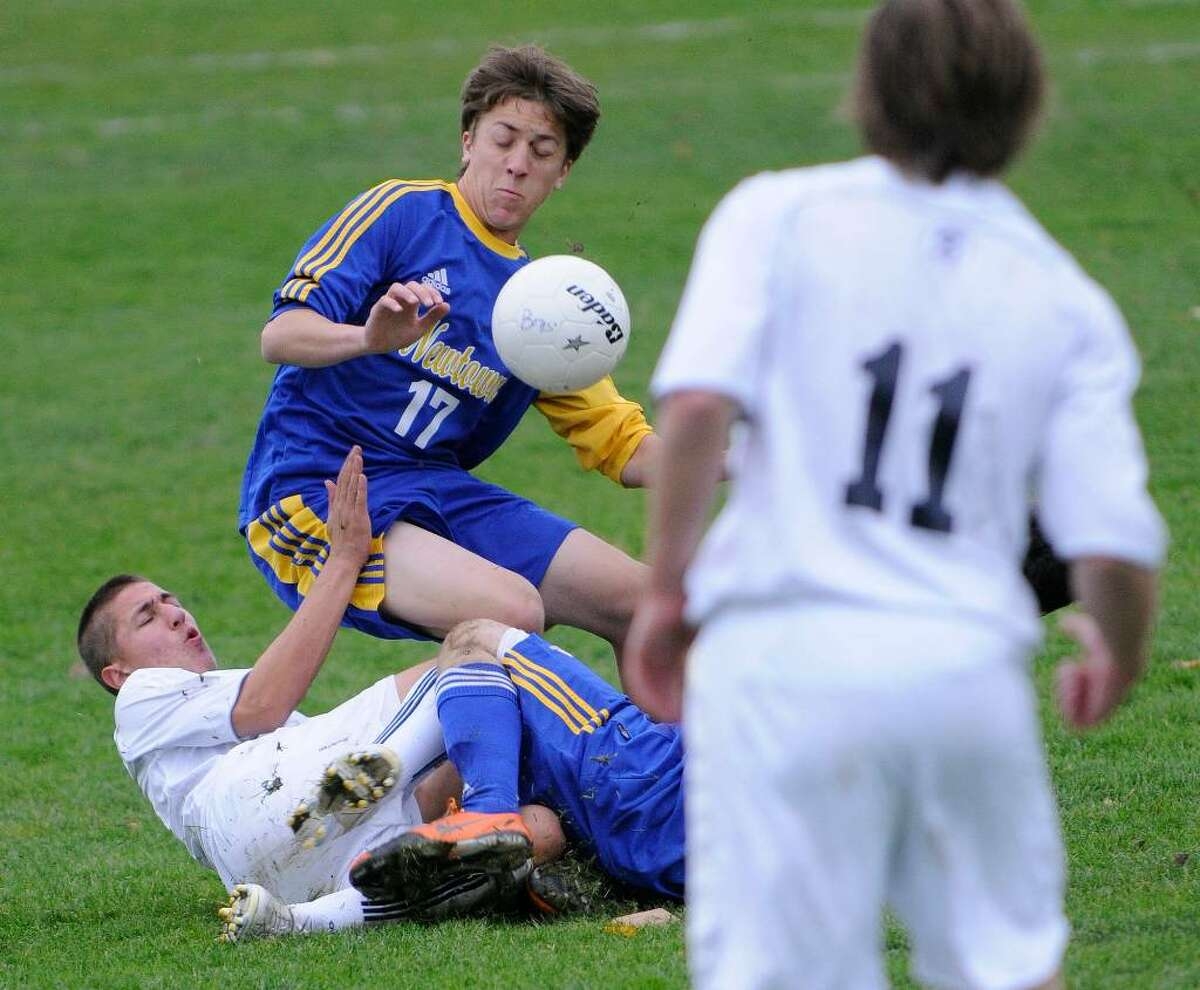 Newtown High School boys varsity soccer team plays Staples at Staples High School in Westport, CT on Thursday, Nov. 11, 2009. Newtown #11 Austin Hall collides with Staples #x and Newtown's #10 Evan Kennedy (obscured, on ground) with Staples #11 Andrew McNair nearby.